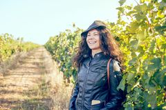 Happy young brunette woman outdoors. Happy young brunette woman winegrower inspecting grape vines in vineyard outdoors in autumn royalty free stock photo