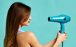 Happy young brunette woman pointing hair dryer on blue mint. Background. Hair style beauty concept royalty free stock image