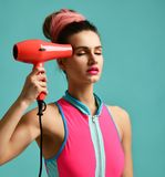 Happy young brunette woman with red hair dryer on blue mint background. Hair style beauty concept Stock Images