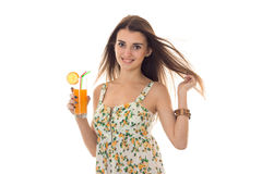 Happy young brunette woman in sarafan with floral pattern drinks orange cocktail and smiling on camera isolated on white Royalty Free Stock Photos