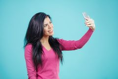 Happy young brunette woman taking selfie stock photography