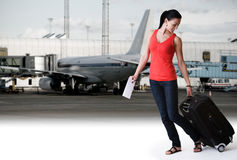Woman walking in airport ready to board an airplan. Happy young brunette woman walking with her travel bag and airline ticket in airport. Outside airport Stock Image