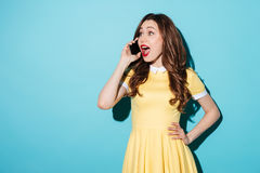 Happy young brunette woman in yellow dress talking by phone. Royalty Free Stock Photos