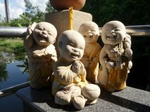Happy young Buddhist monk gang sculpture. Smiling and laughing little monks friend group  clay garden sculpture Royalty Free Stock Photography
