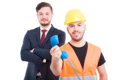 Happy young builder holding phone receiver. And smiling near businessman isolated on white Royalty Free Stock Photos
