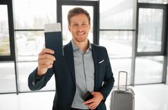 Happy young buisnessman stand in airport hall and show passport with ticket. He looks on camera and smile. Guy has phone. In left hand. His suitcase stand royalty free stock images