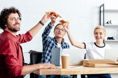 Happy young business colleagues eating pizza and smiling. At camera royalty free stock photos