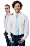 Happy young business executives. Two confident corporates standing and smiling royalty free stock images