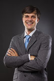 Happy young business man. On gray backing Royalty Free Stock Photos