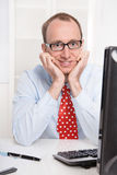 Happy young Business man with glasses and a red tie sitting at d. Esk - satisfied with his job as an engineer Royalty Free Stock Photos