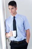 Happy young business man relaxing with coffee cup  in modern off Royalty Free Stock Image