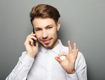 Happy young business man in shirt  gesturing and smiling while t Stock Images
