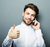 Happy young business man in shirt  gesturing and smiling while t Royalty Free Stock Photo