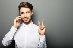Happy young business man in shirt  gesturing and smiling while t Stock Photos