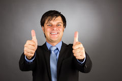 Happy young business man showing thumbs up gesture Stock Photos