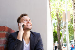 Happy young business man talking on mobile phone outside Royalty Free Stock Image