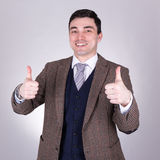 Happy young business man thumbs up over grey. Background stock photo