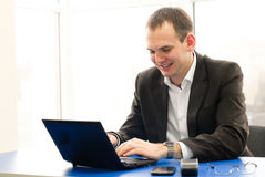 Happy businessman using laptop at office, smiling. Stock Photos