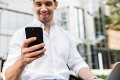 Happy young business man using mobile phone. Close up of happy young business man using mobile phone while sitting outdoors with laptop computer royalty free stock photos