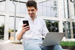 Happy young business man using mobile phone. While sitting outdoors with laptop computer royalty free stock photography