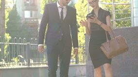 Happy young business partners going to work and using phone. Slowly.  stock video footage