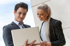 Satisfied business partners reviewing work on laptop. Royalty Free Stock Photo
