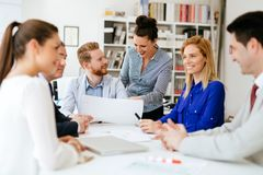 Happy business people in office. Happy young business people brainstorming in office royalty free stock photography