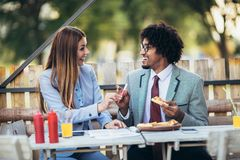 Young business team eating pizza in outdoor cafe.Business,food and people concept. Happy young business team eating pizza in outdoor cafe.Business,food and royalty free stock photography