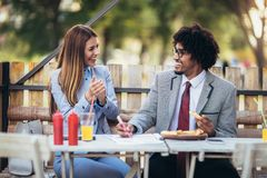 Young business team eating pizza in outdoor cafe.Business,food and people concept. Happy young business team eating pizza in outdoor cafe.Business,food and royalty free stock photo