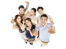 Happy young business team with thumbs up gesture Royalty Free Stock Photos