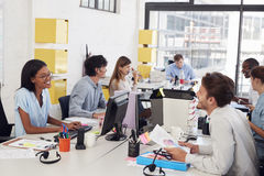 Happy young business team working in a busy open plan office Stock Photo