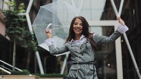 Happy young business woman dancing with umbrella checking if the rain stop. She smiling and enjoying the end of the rain. On business centre background stock video
