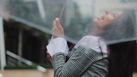 Happy young business woman dancing with umbrella checking if the rain stop. She smiling and enjoying the end of the rain. On business centre background stock video footage