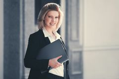 Happy young business woman with file folder at office building stock images