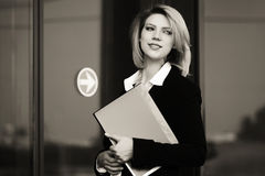 Happy young business woman with a folder at office building Royalty Free Stock Images