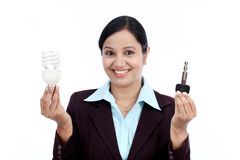 Happy young business woman holding bulb and key Royalty Free Stock Photos
