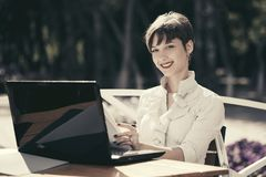 Happy young business woman with laptop at sidewalk cafe. Happy young business woman with laptop working at sidewalk cafe Stock Image