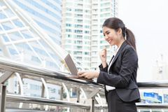Happy young business woman with laptop working outdoor with urba. N background Stock Photography