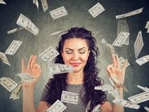 Woman meditating under money rain. Happy young business woman meditating under money rain falling down cash royalty free stock photos
