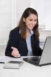 Happy young business woman sitting at desk with computer and onl Stock Photos