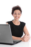 Happy young business woman sitting at desk with laptop. Royalty Free Stock Image