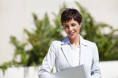 Happy young business woman smiling with a laptop Stock Image