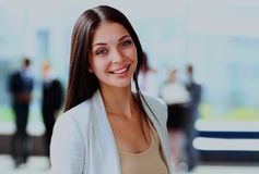 Happy young business woman standing in front of her team. Smiling confident business woman looking at camera with her colleagues in background at office Stock Image