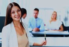 Happy young business woman standing in front of her team. Smiling confident business women looking at camera with her colleagues in background at office Royalty Free Stock Photo