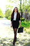 Happy young business woman is walking in city park Royalty Free Stock Photography