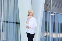 Happy young business woman walking and talking on cell phone Royalty Free Stock Image