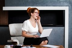 Young woman working in the office. Happy young business woman works sitting in a chair in the office Royalty Free Stock Images