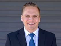 Happy young businessman with a beaming smile. Happy young businessman with a beaming warm friendly smile in a head and shoulders portrait against a grey wall Royalty Free Stock Photo