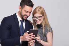 Happy young businessman and businesswoman using tablet Royalty Free Stock Images