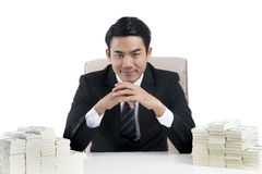 Happy Young businessman clasped hands and large pile of money on. Happy young businessman in black suit sitting and clasping hands with two large piles of money Stock Images